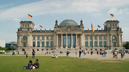 bundestag : Berlin, Germany, May 2018: The urban life of Berlin - tourists and locals are resting on the lawn near the building of the Bundestag