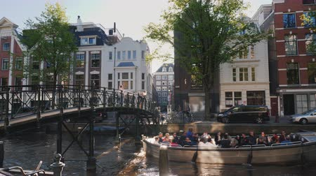 işlemek : Amesterdam, Netherlands, May 2018: Scenic landscape - a boat with tourists swims under the bridge along one of the canals of the city. Through the ancient houses the sun shines.