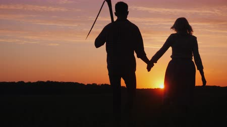 ogrodnik : A couple of farmers man and woman walking away into the field at sunset. A man carries a braid on his shoulder Wideo