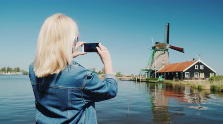 голландский : A young woman is photographing old windmills in the Netherlands. Travel Europe and the Netherlands concept