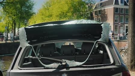 property theft : A car with a broken rear window. Victim of thieves and vandals in the center of the city. In the center of Amsterdam on the bank of the canal Stock Footage