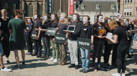 cent : Amesterdam, Netherlands, May 2018: People in black T-shirts and white masks are protesting against animal cruelty. Keep in the chickens tablets and laptops. In the central square of the city