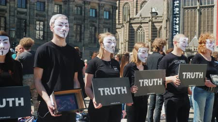pravda : Amesterdam, Netherlands, May 2018: Young people in white masks are protesting against cruel ornithosis with animals. Dam Square in Amsterdam