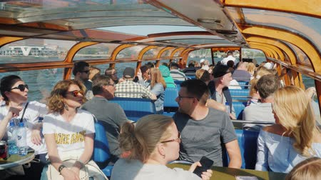 бортовой : Amesterdam, Netherlands, May 2018: A group of passengers inside a small cruise ship with a glass ceiling. Cruise through the canals of Amsterdam Стоковые видеозаписи