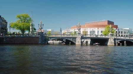 múlt : Amesterdam, Netherlands, May 2018: Cruise through the canals of Amsterdam. Swim past the building of the Opera and Ballet Theater