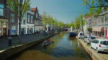 holandês : Delft, Netherlands, May 2018: Beautiful channel in the quiet Dutch city of Delft. A boat will be running along the water, beautiful buildings along the banks. Tourism in the Netherlands