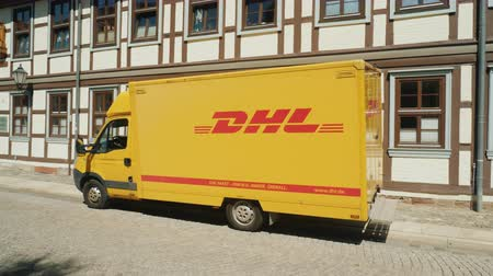 korporacja : Wernigerode, Germany, May 2018: The wagon of the postal service DHL stands on a quiet street in a German town on the background of a typical architecture for Germany. Side view