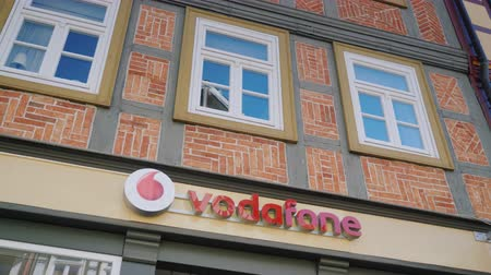 inc : Wernigerode, Germany, May 2018: The sign of Vodafone is one of the largest mobile operators in Europe. On the facade of an old German house with a recognizable style of construction