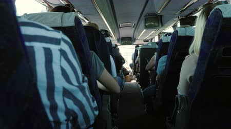 crouch : Inside the passenger bus. Rows of seats with passengers, rear view