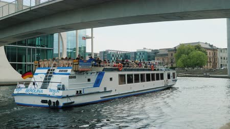 sas : Berlin, Germany, May 2018: A pleasure boat with tourists aboard sails along the river near the bridge