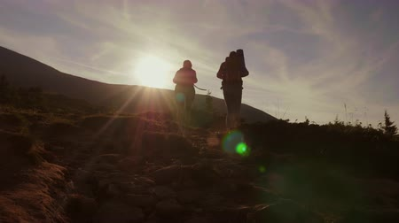 sıkı : Climbing the mountain at dawn. Two tourists climb up the mountain path in the sun