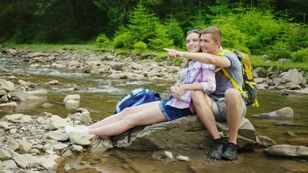 backpacken : A loving couple of tourists with backpacks rests in a picturesque place near a mountain river. They embrace and sit on a rock. Happy holidays