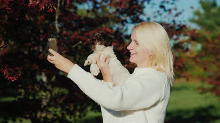 selfie girl : A young woman with a puppy in her hands takes a picture of herself using her phone. Photo with your pet