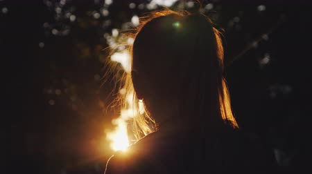 szőke : Silhouette of a girl looking at the sunset in the park. The sun beautifully illuminates her blond hair. Rear view
