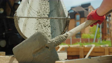 manual labor : Pour concrete from the mixer into the formwork. In the background, blurred new buildings. Construction of cottages concept Stock Footage