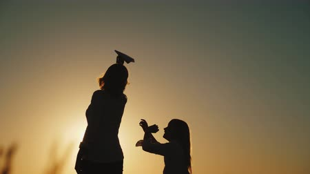 letec : Happy mother with her daughter playing with a paper airplane at sunset