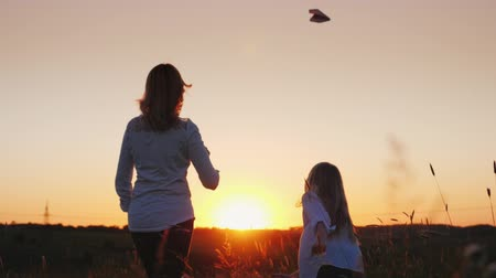 letec : Mom and daughter launch paper airplanes into the air. Slow motion video Dostupné videozáznamy