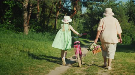 uzun ömürlü : Grandma is walking with her granddaughter. The girl drives a bicycle, the grandmother carries a basket with wild flowers. Active seniors concept
