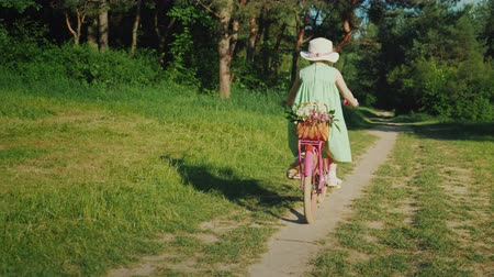 ciclismo : A girl in a green summer dress is riding along a path in the forest. Carries a basket of flowers. Active summer vacation concept Stock Footage