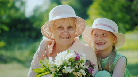 filha : Portrait of a happy elderly woman with her granddaughter. Hold a basket with wild flowers, look at the camera