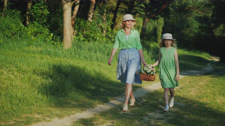 filha : Mom and daughter are walking along a path in the forest, carrying a basket with wildflowers. Happy parents with children Vídeos