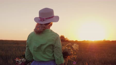 cesta : A romantic woman with a hat and a bouquet of wildflowers admires the sunset over the wheat field. Rear view
