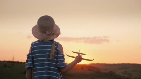pigtailler : A girl with pigtails and a hat playing with a wooden airplane at sunset. The dream of long-distance travel is a concept Stok Video