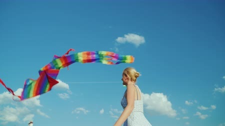 annelik : Happy woman as a child plays with an air kite on a background of pure blue sky