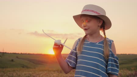 pigtailler : A girl with pigtails and a hat playing with a wooden airplane at sunset. Front view. The dream of long-distance travel is a concept