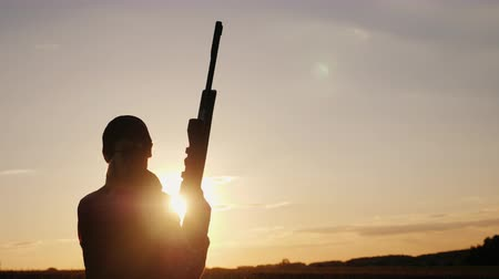 game hunting : Silhouette of a woman with a rifle in the rays of a sunset. Sports shooting