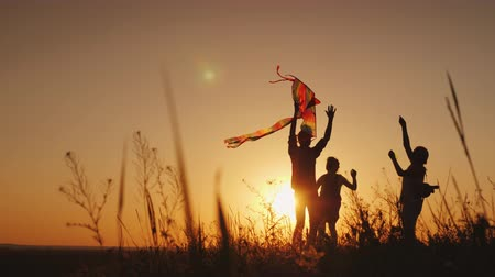 коршун : Happy family playing with a kite at sunset. Mom, Dad and daughter are happy together