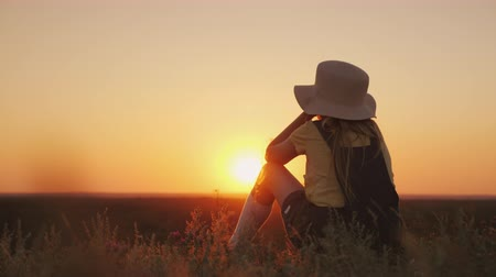 insult : A girl in a hat admires the sunset in a picturesque place. She sits on a hill, her chin on her hands, bored or offended Stock Footage