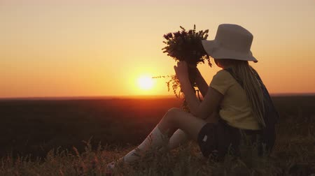 insult : A girl with a bouquet of wildflowers in her hands is looking at a beautiful sunset. Sits on a hill in a picturesque place Stock Footage