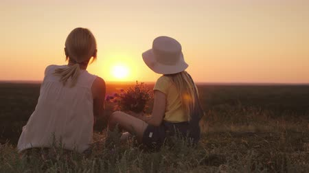 filha : Mom and little daughter are sitting on a hill, admiring the sunset. In the hands of wild flowers. Summer with kids and holidays