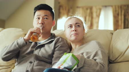 межрасовый : Young couple watching television together. A man is drinking beer, a woman is holding a packet of snacks Стоковые видеозаписи