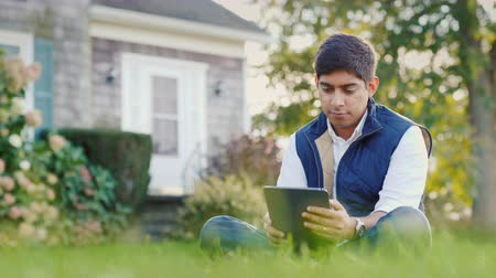 sul : An Indian man uses a tablet in the backyard of his house. Sits on the lawn