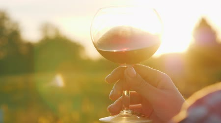 kırmızı şarap : Tasting wine at sunset. The light shines beautifully on a glass of red wine