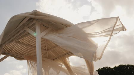 arenoso : Tent from the sun on the beach. Fabric fluttering in the wind at sunset. Comfortable rest concept