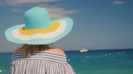 arka görünüm : A woman in a hat looks at the azure sea. Dream vacation concept