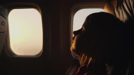 aircraft cabin : Silhouette of a child sleeping in an airplane. Outside the window, the sun rises, a trip with children concept