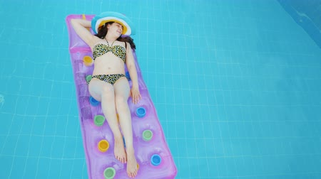 volný čas : Young sexy woman sunbathing on an inflatable mattress, luxuriate under the sun in the pool Dostupné videozáznamy