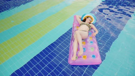 colchão : An attractive woman is floating on an inflatable mattress in the pool. Sweet under the rays of the sun. Woman on vacation concept
