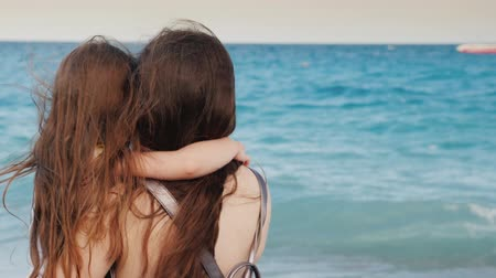 filha : A young mother with brown hair hugs her little daughter with long flowing hair against the blue sea