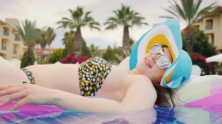 roupa de banho : Girl tourist in a swimsuit resting in the pool on an inflatable mattress in a multi-colored hat and sunglasses. Side view
