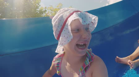 filha : Mom and daughter are going fun down the water slide, laughing. Happy family on vacation