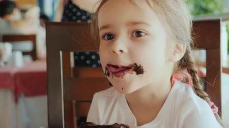 tápláló : A cool little girl is eating a sweet bun, her face is smeared with chocolate