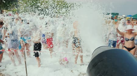 deli : Kemer, Turkey, June 2018: A crowd of vacationers have fun on the beach under the streams of foam. Foam party on the beach, entertainment for tourists in Turkey Stok Video