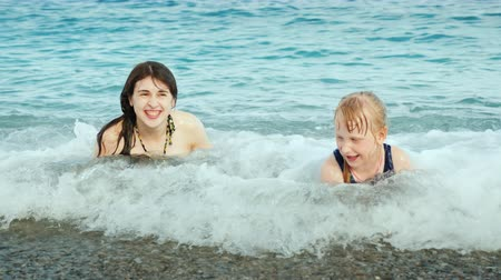 hazugság : A young active mother with a girl is playing fun on the sea waves on the beach, laughing, somersaulting