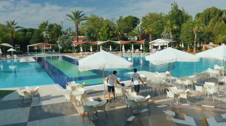 wipe off : Kemer, Turkey, June 2018: The hotel staff removes the territory in a five-star hotel. Near the pool there are tables and umbrellas - everything is a comfortable rest in Turkey