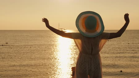 breathing fresh air : A young woman in a light dress and hat meets the dawn at the sea. A ship is visible in the distance. Dream of the perfect vacation concept
